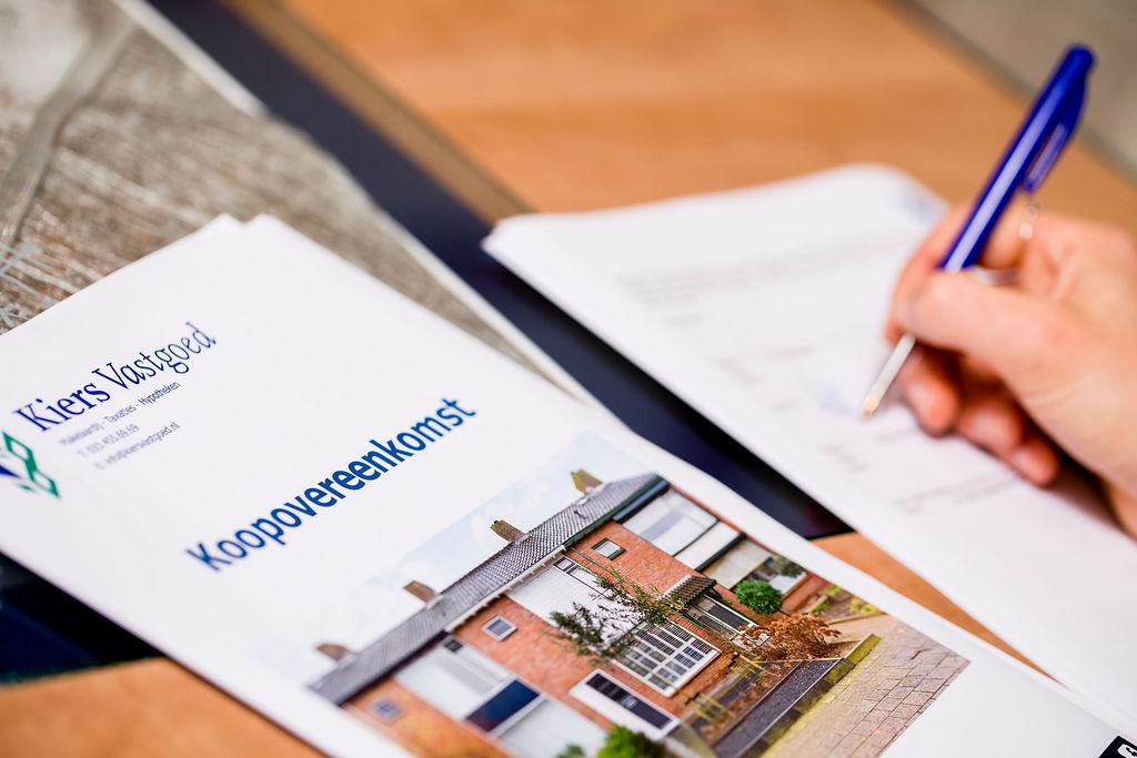 Koper krijgt uitleg bij ondertekenen van de koopovereenkomst aangekochte woning