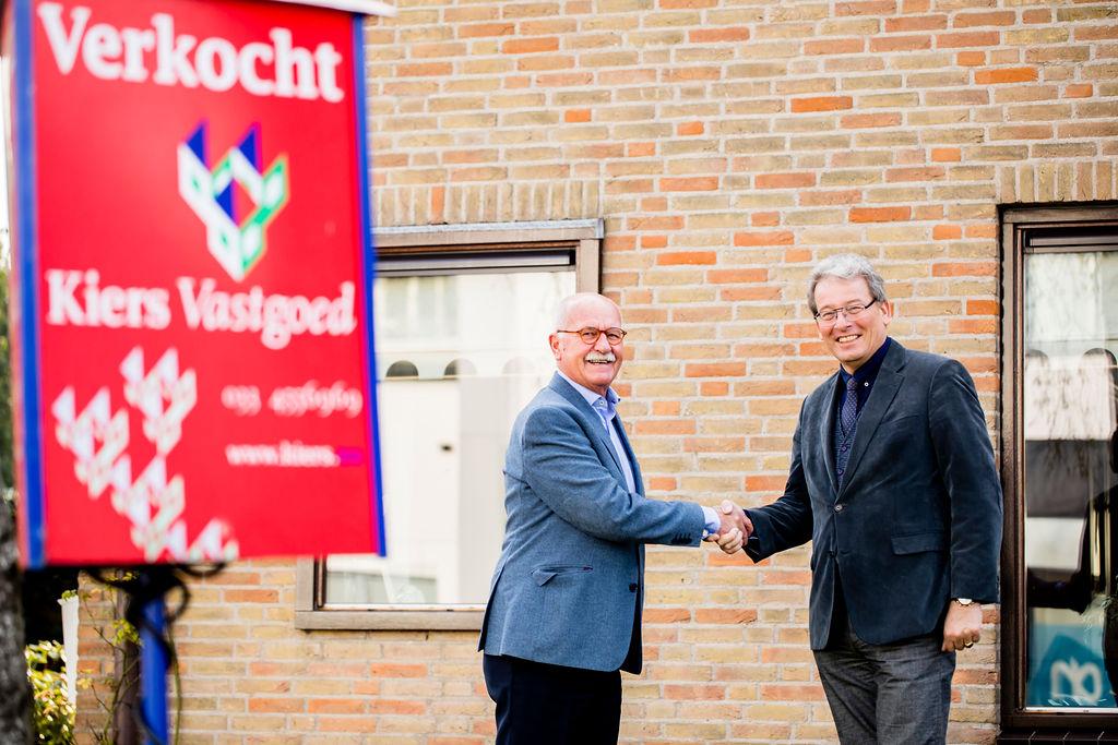 Makelaar Jan Kiers feliciteert verkoper in de tuin met de verkoop van zijn woning